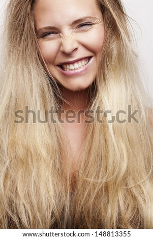Portrait of a blond girl making a face and having fun. Studio shot, shallow depth of field. - stock photo