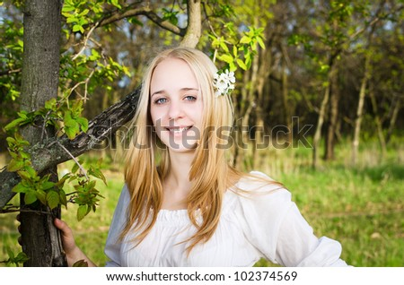 Portrait of a blond girl with green tree - stock photo