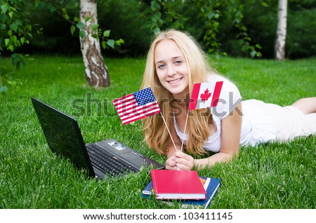 Portrait of a blond girl with USA and Canadian flags on the grass with laptop - stock photo