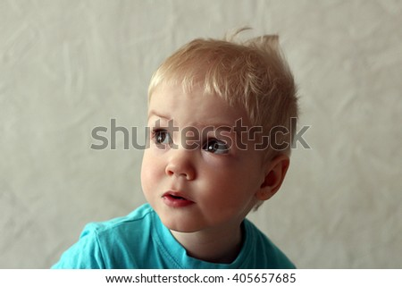 Portrait of a blond-haired, blue-eyed, curly-haired boy  - stock photo