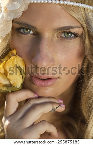 Portrait of a blond haired girl with yellow rose - stock photo