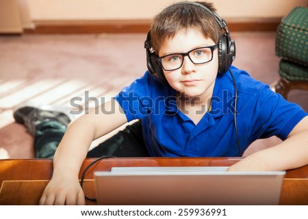 Portrait of a blond kid wearing headphones and playing a video game on a laptop computer - stock photo