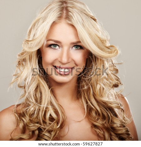 Portrait of a blond lady with a beautiful hair on grey background - stock photo