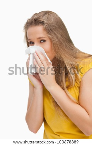 Portrait of a blond woman blowing against white background