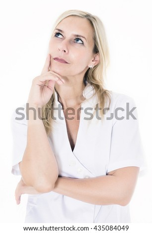 portrait of a blond woman in a white overall looking thoughtful - stock photo