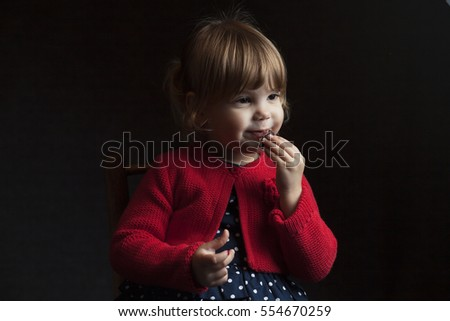 Portrait of a blonde caucasian cute three year old baby girl, eating a biscuit or cookie, wearing blue polka dot dress, sitting on a wooden toy chair