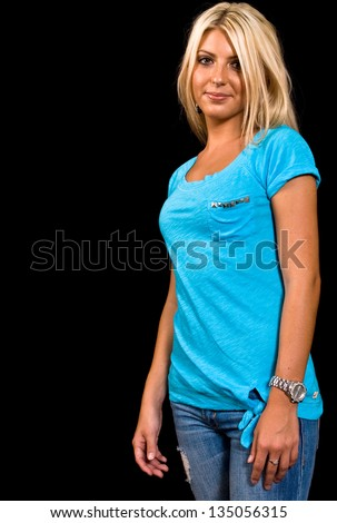Portrait of a blonde Caucasian female with brown eyes in a blue shirt, ripped blue jeans on black background. - stock photo