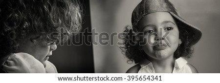 Portrait of a blonde female child smiling with the tongue out and a jeans hat and thinking child close up in black and white