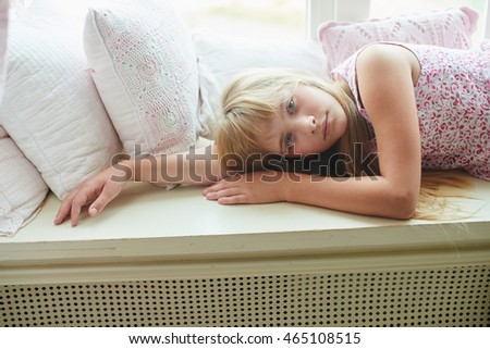 Portrait of a blonde girl lying next to the pillows at home
