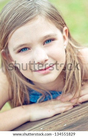 Portrait of a blonde girl outdoors in the park - stock photo