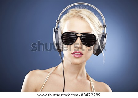 Portrait of a blonde girl with black sunglasses and headphones. - stock photo