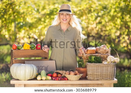 Portrait of a blonde smiling over a table of organic food - stock photo