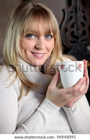 Portrait of a blonde woman drinking a hot drink - stock photo