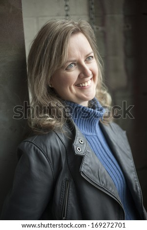 Portrait of a blonde woman in a warehouse. - stock photo
