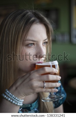 Portrait of a blonde woman with blue eyes drinking a goblet of beer. - stock photo