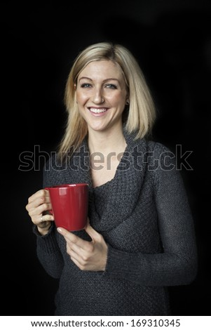 Portrait of a blonde woman with blue eyes holding a red coffee cup. - stock photo