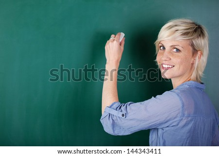 Portrait of a blonde young woman writing on chalkboard - stock photo
