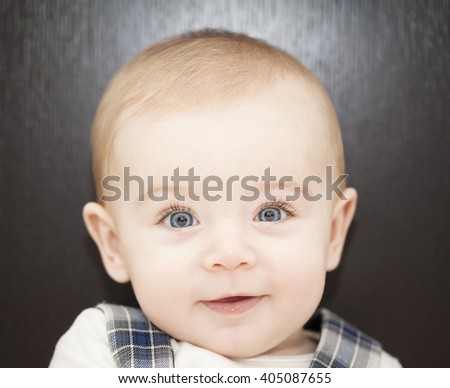 Portrait of a blue eyes baby leaning on the bed - stock photo