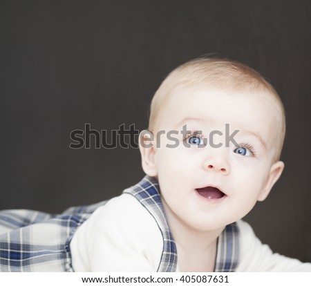Portrait of a blue eyes baby leaning on the his bed