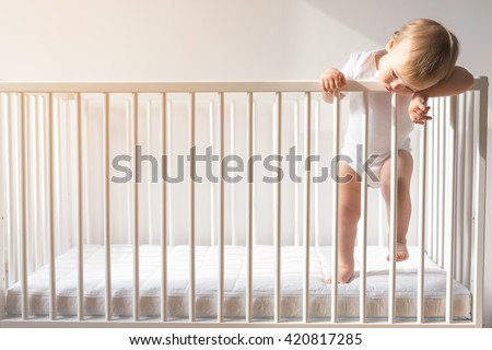 Portrait of a bored baby standing in a drib. - stock photo