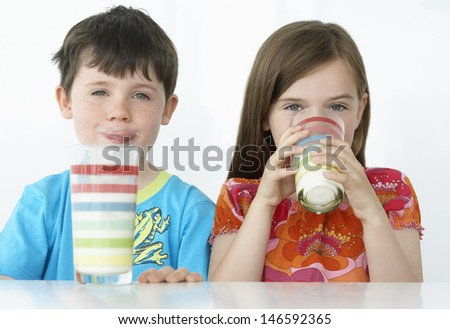 Portrait of a boy and girl drinking milk from colorful glasses - stock photo