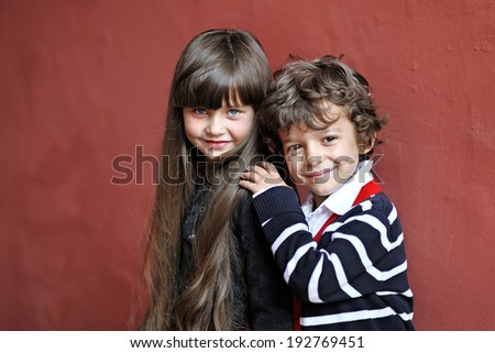portrait of a boy and girl in autumn - stock photo