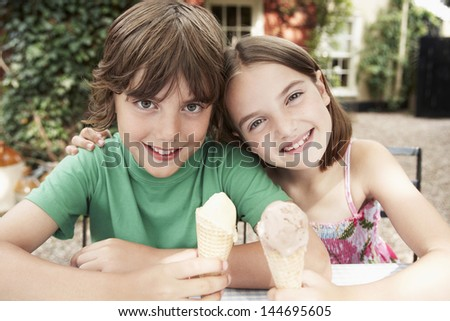 Portrait of a boy and girl with ice cream cones at the backyard table - stock photo