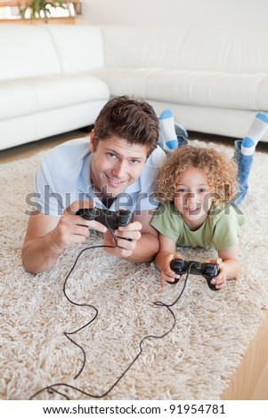 Portrait of a boy and his father playing video games while lying on a carpet - stock photo