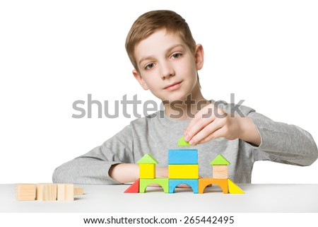 Portrait of a boy building house of wooden blocks - stock photo