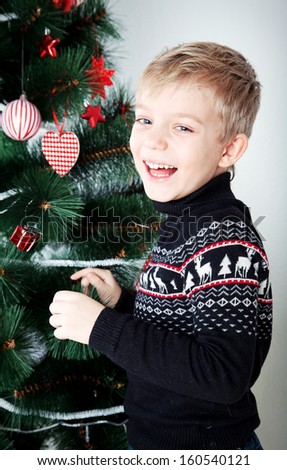 portrait of a boy decorating cristmas tree and have fun - stock photo