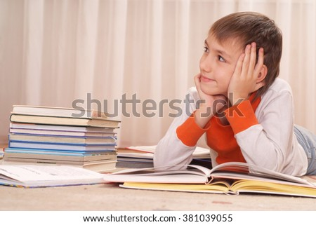 Portrait of a boy does homework at home alone - stock photo