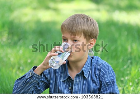 Portrait of a boy drinking water from a glass in nature