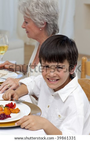 Portrait of a boy having dinner with his family at home - stock photo