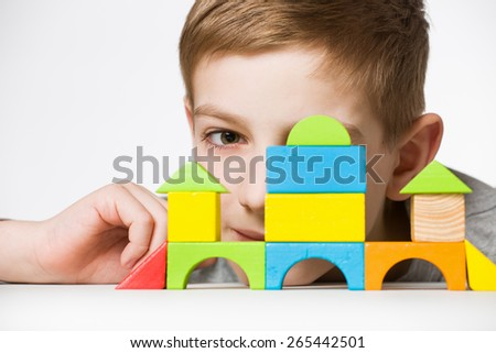 Portrait of a boy hiding behind house made of wooden blocks - stock photo