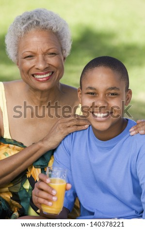 Portrait of a boy holding glass of orange juice with grandmother - stock photo