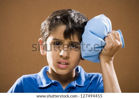 Portrait of a boy holding ice pack to his head - stock photo