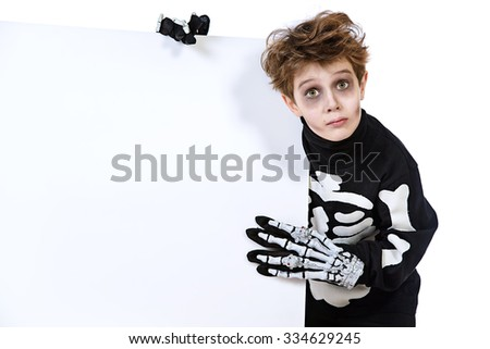 Portrait of a boy in a costume of skeleton holding white board. Halloween party. Copy space. Isolated over white. - stock photo
