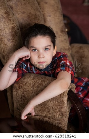 Portrait of a boy in a shirt sitting in a chair