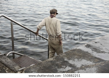 portrait of a boy in old retro clothes and cap standing by the water looking poor and dirty, an apprentice - stock photo