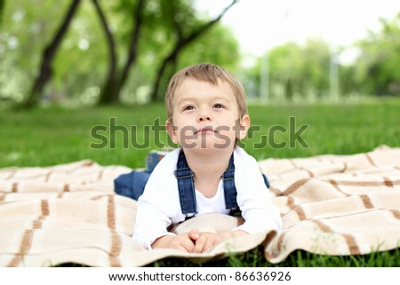 Portrait of a boy laying on the blanket in the park - stock photo