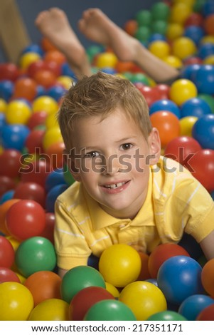 Portrait of a boy lying in a ball pool and smiling