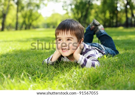 Portrait of a boy lying on the grass in the park