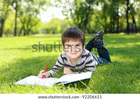 Portrait of a boy lying on the grass with a book in the park