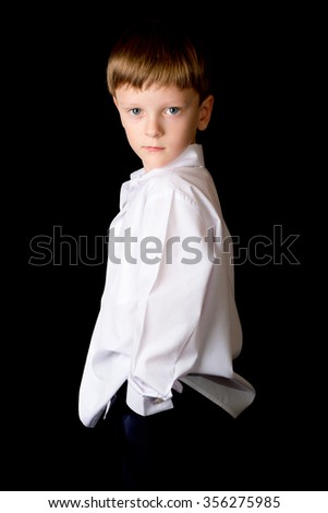 Portrait of a boy on a black background with the white shirt. Blue eyes blond. Different camera angles while standing.