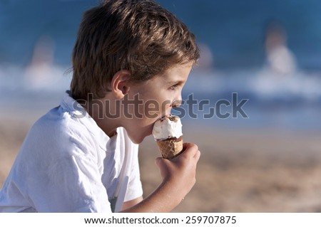 Portrait of a boy on the beach, eating ice cream - stock photo