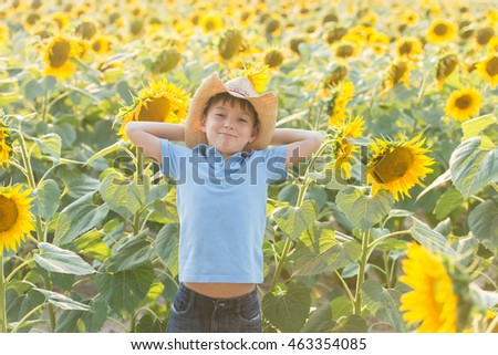 Portrait of a boy on the field of sunflowers, small farmer