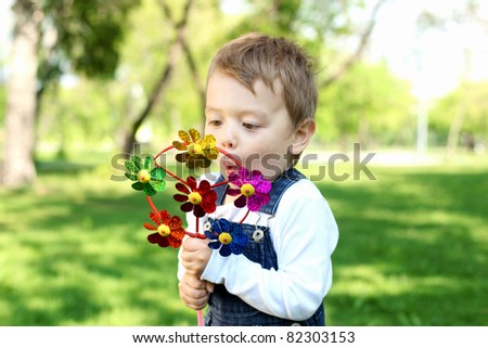 Portrait of a boy palying with a windmill in the park - stock photo