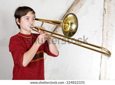 portrait of a boy playing the trombone - stock photo