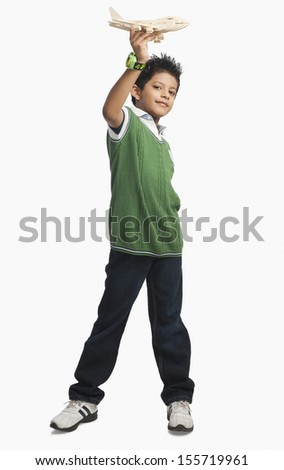 Portrait of a boy playing with a toy airplane - stock photo