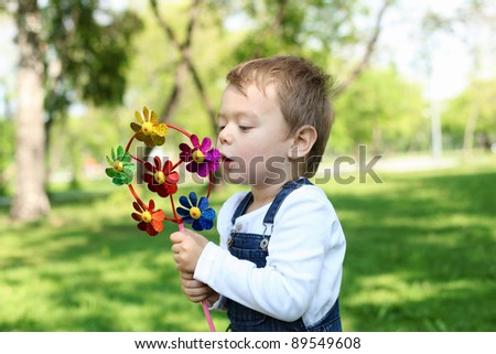 Portrait of a boy playing with a windmill in the park - stock photo
